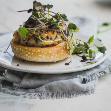 A close up image of a cauliflower burger on a white plate.