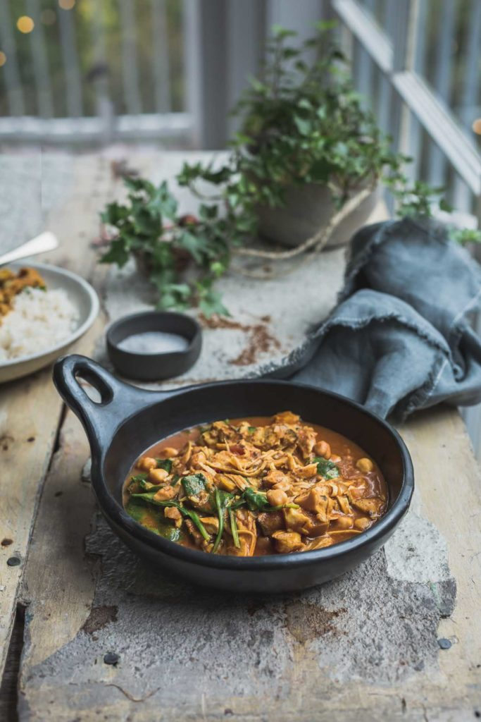 A tabletop image of a rustic black bowl full of mushroom and chickpea vegan tikka masala with another serving in a white bowl nearby. The table is sitting next to a window where we can see greenery outside.