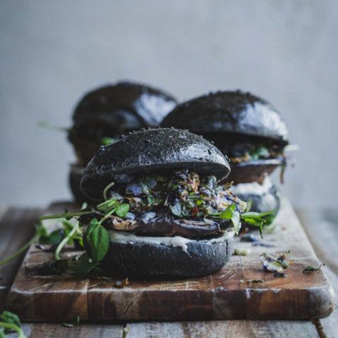 Three mushroom burgers on a wooden board.