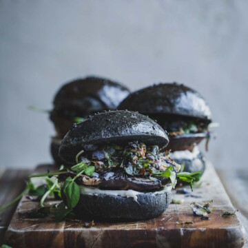 A close up image of a mushroom burger on a wooden board.