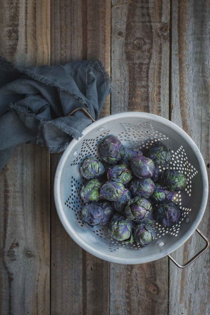 Overhead process image of a rustic colander full of freshly washed purple Brussels sprouts sitting on a distressed wooden bench