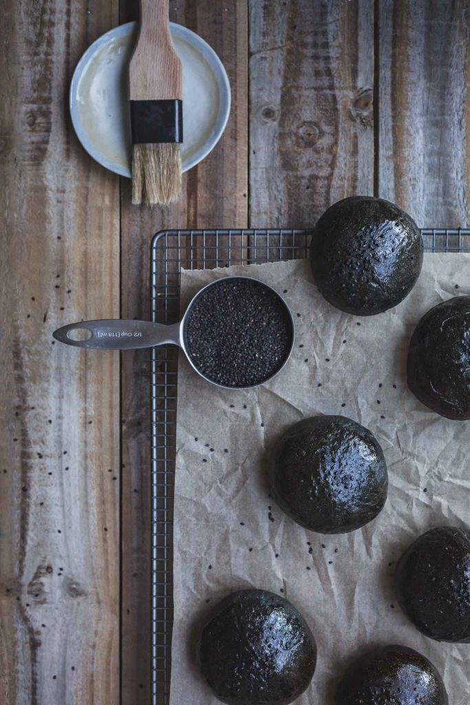An overhead process shot of a rack of unbaked charcoal buns, a cup of black chia seeds and a pastry brush on a distressed wooden board