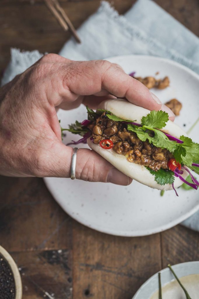 Close-up overhead shot of a man's hand holding a vegan bao bun filled with peking tempeh and greens over a white plate and rustic wooden table.