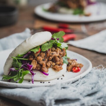 A close up image of a bao bun filled with temper and greens.