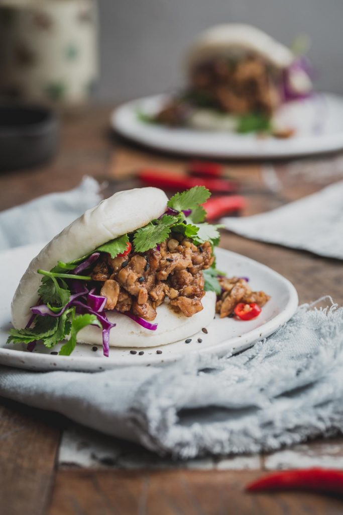 Close up image of a bao bun filled with peking tempeh and greens on a white plate with a grey napkin underneath. Another bun sits in the distance in a rustic wooden table.