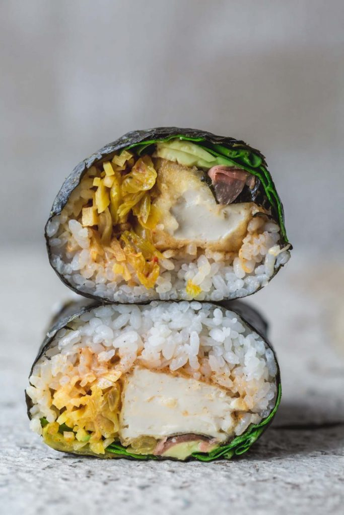 A vegan crispy tofu sushi burrito cut in half and stacked to show inside | sitting on rustic white bench