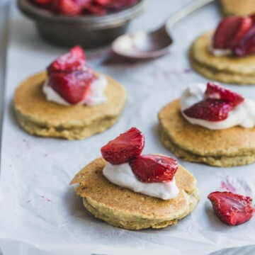 Small coconut banana pancakes with cream and strawberries on a white background