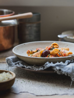 A bowl of pasta with olives on a bench