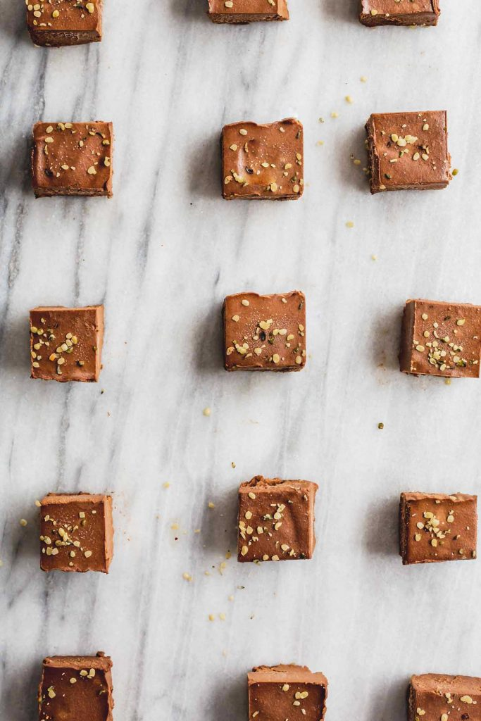 an overhead image of a grid layout of sweet potato chocolate squares on a marble background