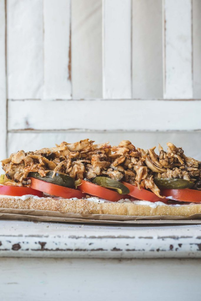 A front on, close-up image a vegan o'boy with succulent oyster mushrooms, pickle and tomato on a bowl sandwich bag