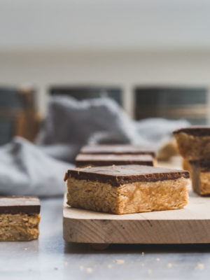 Peanut butter oatmeal squares with chocolate on a wooden board
