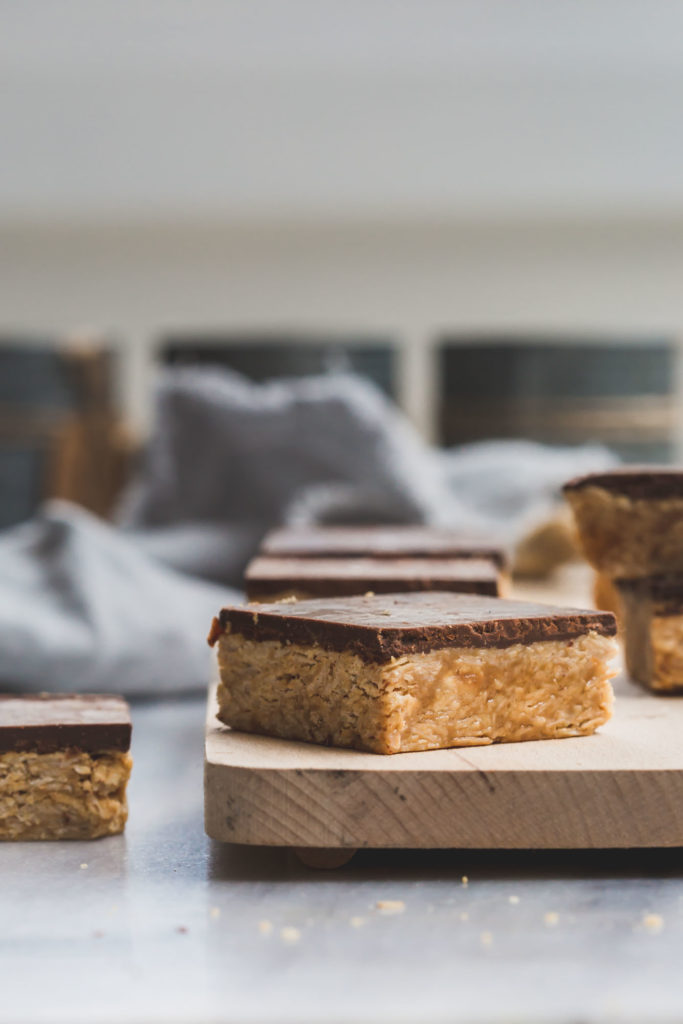 close up image of no-cook peanut butter and chocolate oat squares on a wooden board