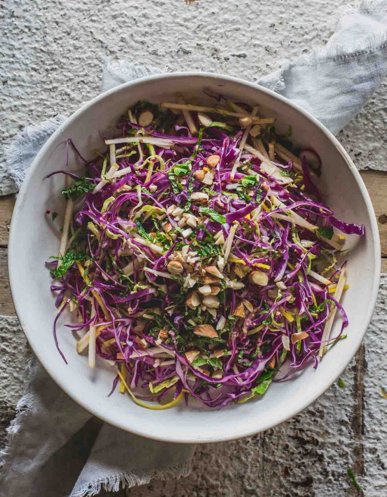 A overhead image of a white bowl full of detox salad with orange miso dressing