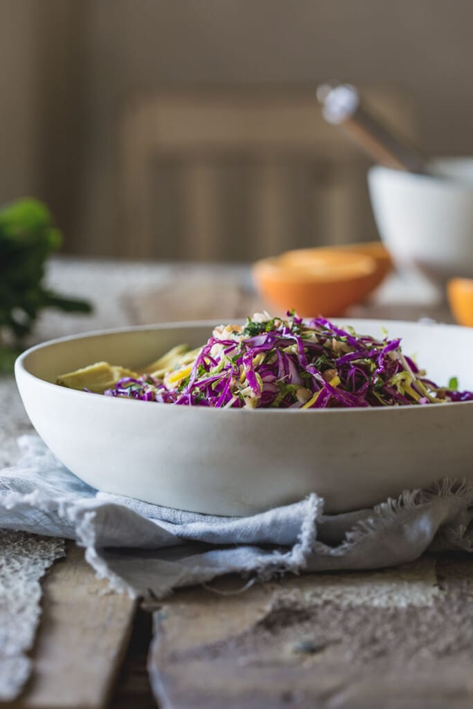 table setting featuring a large bowl of detox salad with orange missing dressing