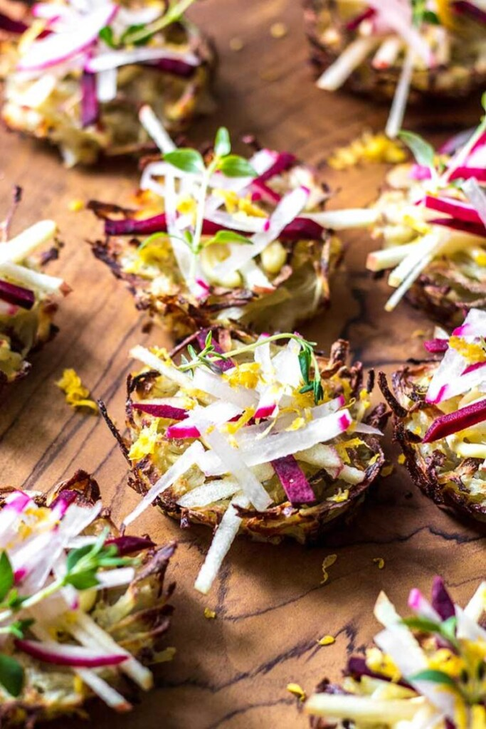 35 Vegan Party Food Recipes. No.1 Potato Nests from Quite Good Food sitting on a wooden chopping board.