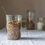 Jar of almond butter maple granola sitting on a white-clothed table, squared image
