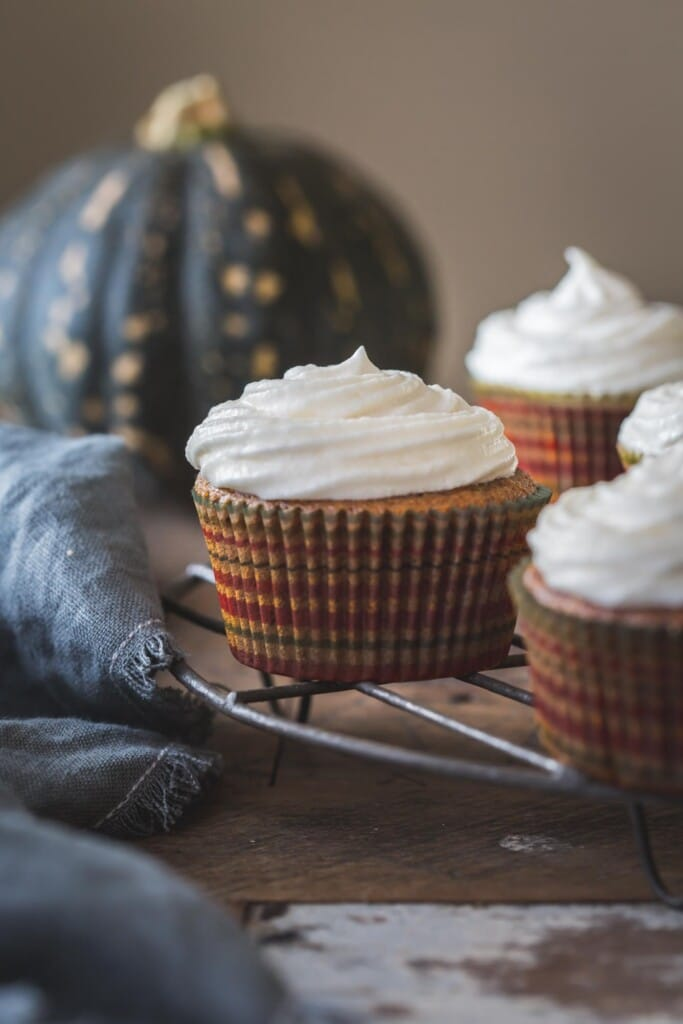 close up image of vegan pumpkin cupcakes on a wire cake stand