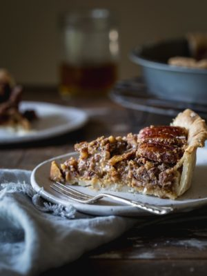 A slice of vegan pecan pie on a plate with a napkin sitting on a wooden table