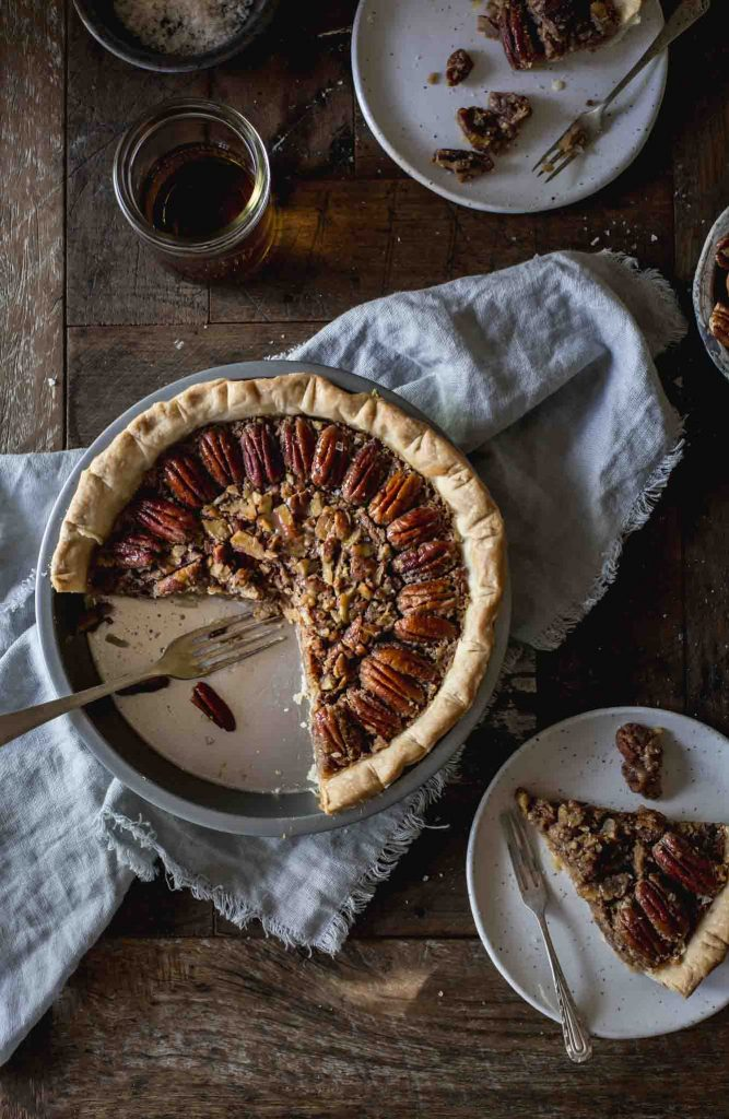 Flat lay image of cut into vegan pecan pie and served portions on plates
