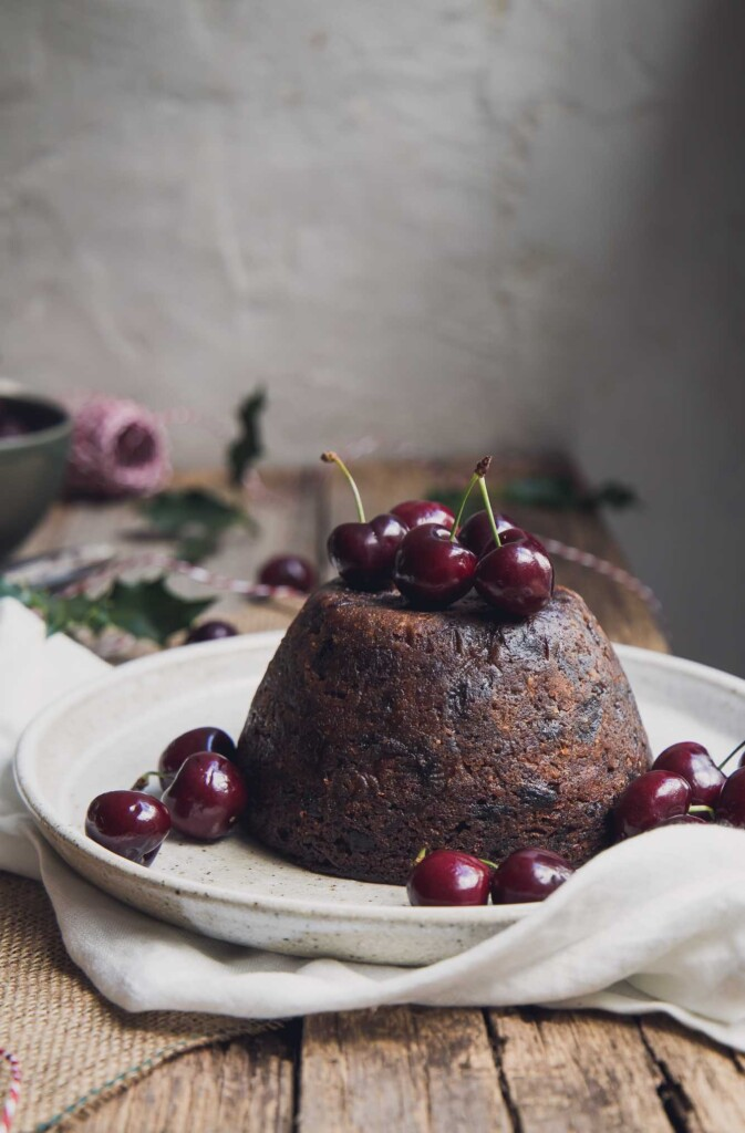 Vegan Christmas pudding on a serving plate with fresh cherries