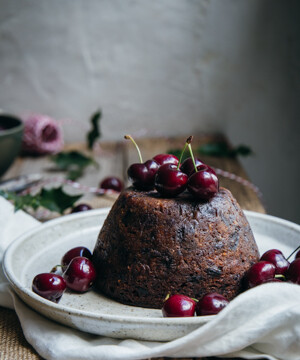 A Christmas pudding with cherries on a wooden table
