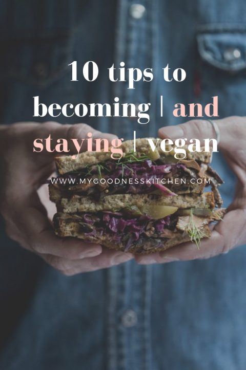 "A picture of a man's hands holding a large vegan sandwich with the text ""10 tips to becoming and staying vegan"" overlay"