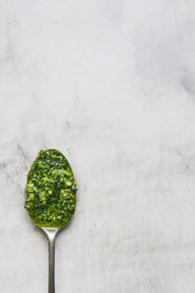 flat lay image of a rustic spoon filled with vegan kale pesto offset to the bottom corner of the image