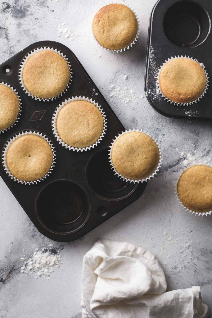 Flat-lay image of freshly baked vegan vanilla cupcakes in 2 rustic baking trays