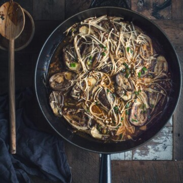A noodle stir fry in a pan on a wooden table