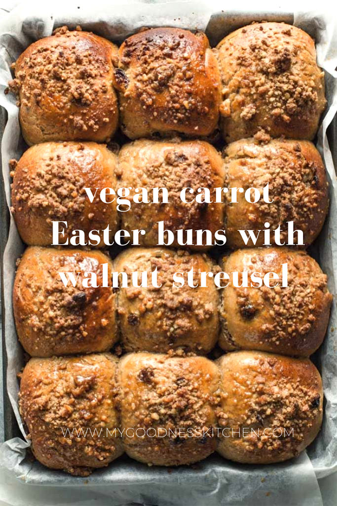 flatlay, full frame image of a full tray of vegan carrot easter buns fresh from the oven topped with a walnut crumble with a title text overlay
