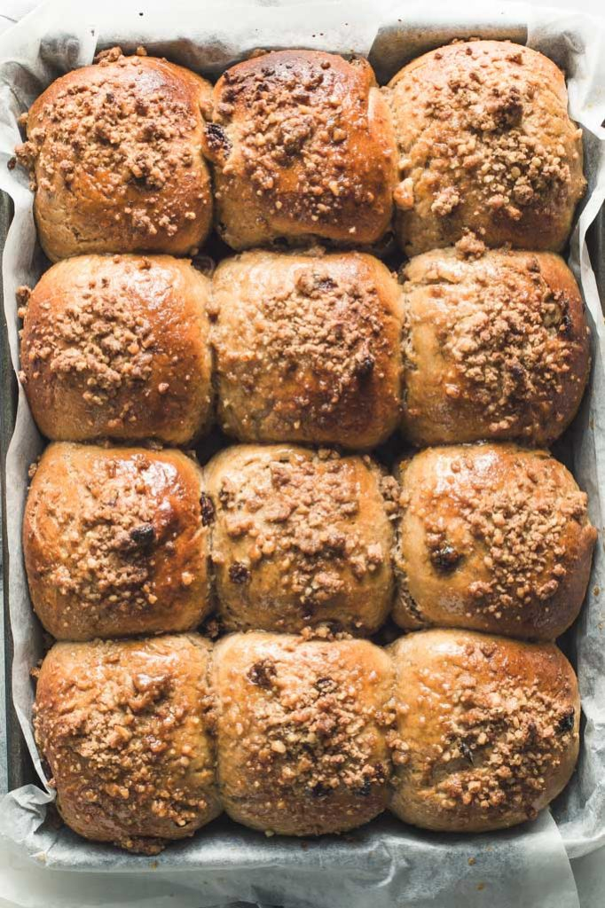 An overhead image of a full tray of freshly baked carrot Easter buns with walnut streusel