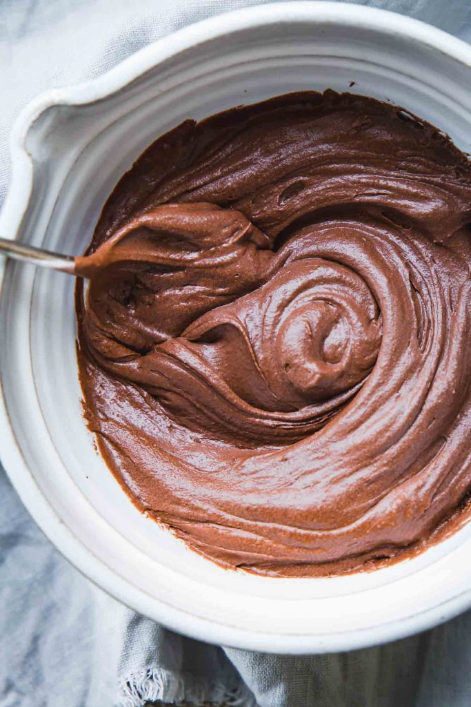 Close-up image of a white mixing bowl full of vegan chocolate frosting swirls