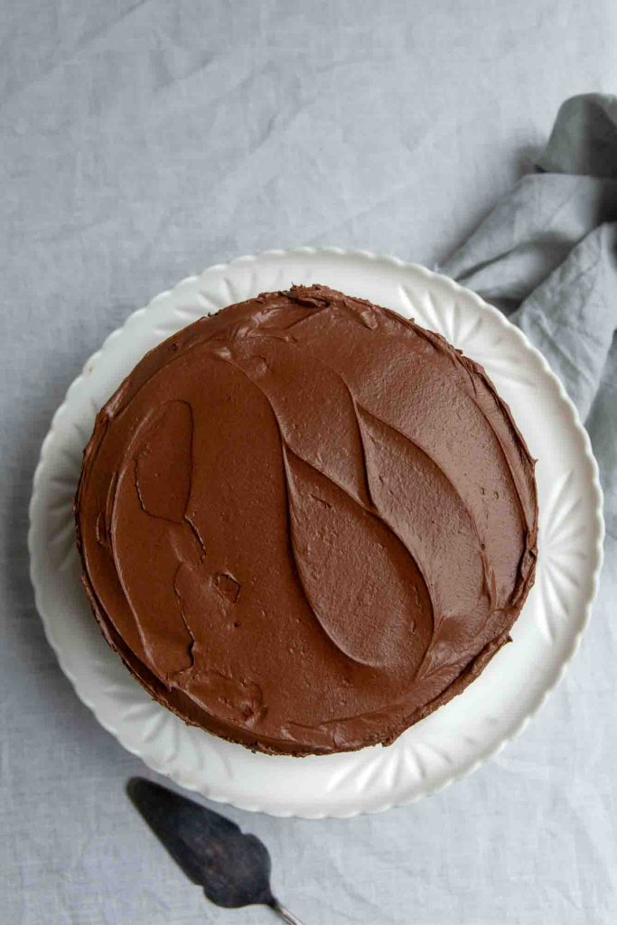 overhead image of a freshly frosted vegan chocolate cake sitting on a white plate with a grey textured napkin nearby