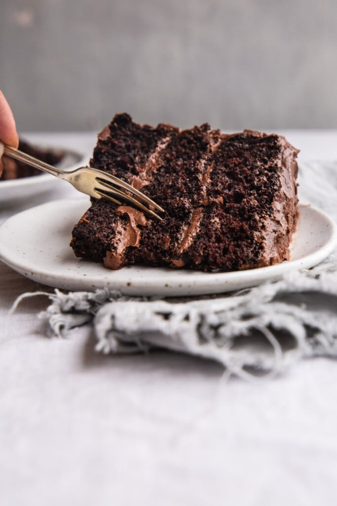 A front-on image of a frosted slice of vegan chocolate cake being cut in to with a fork.
