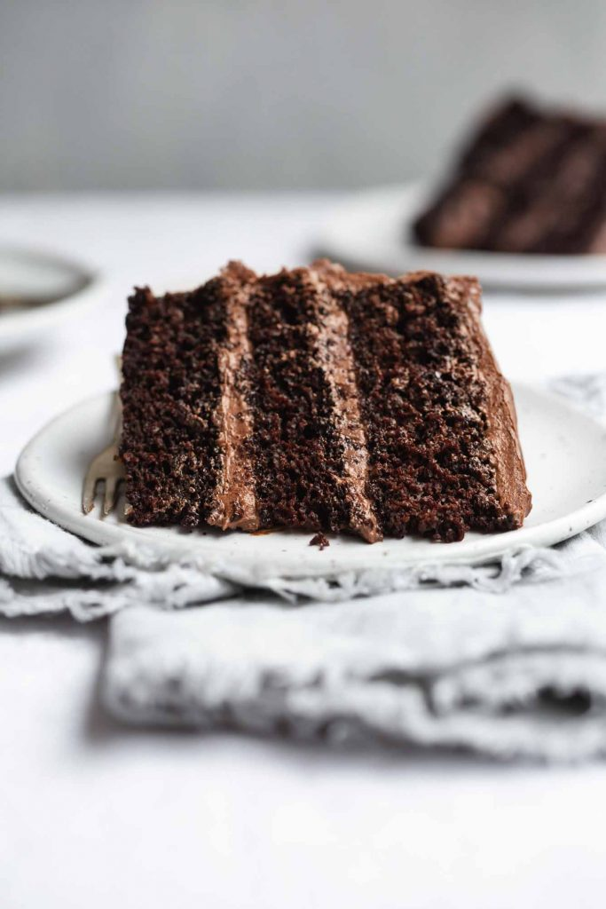 A front-on image of a slice of frosted vegan chocolate cake laying on a white plate on a grey napkin with another pslice on a plate sitting off to the back right