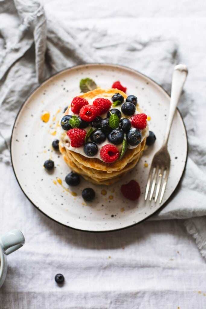 An over-head image of a stack of whole wheat vegan pancakes topped with vegan yoghurt and fresh berries sitting on a white plate on a crinkled linen tablecloth.