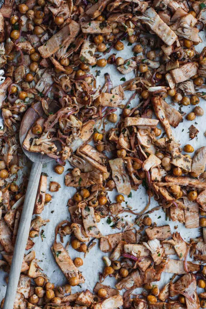 Close-up overhead image of freshly cooked vegan shawarma with roasted jackfruit and chickpeas on a roasting tray with a wooden spoon in the background