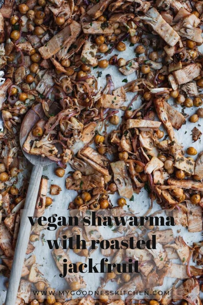 Close-up overhead image of freshly cooked vegan shawarma with roasted jackfruit and chickpeas on a roasting tray with a wooden spoon in the backgroundClose-up overhead image of freshly cooked vegan shawarma with roasted jackfruit and chickpeas on a roasting tray with a wooden spoon in the background. Title text overlay in dark grey.