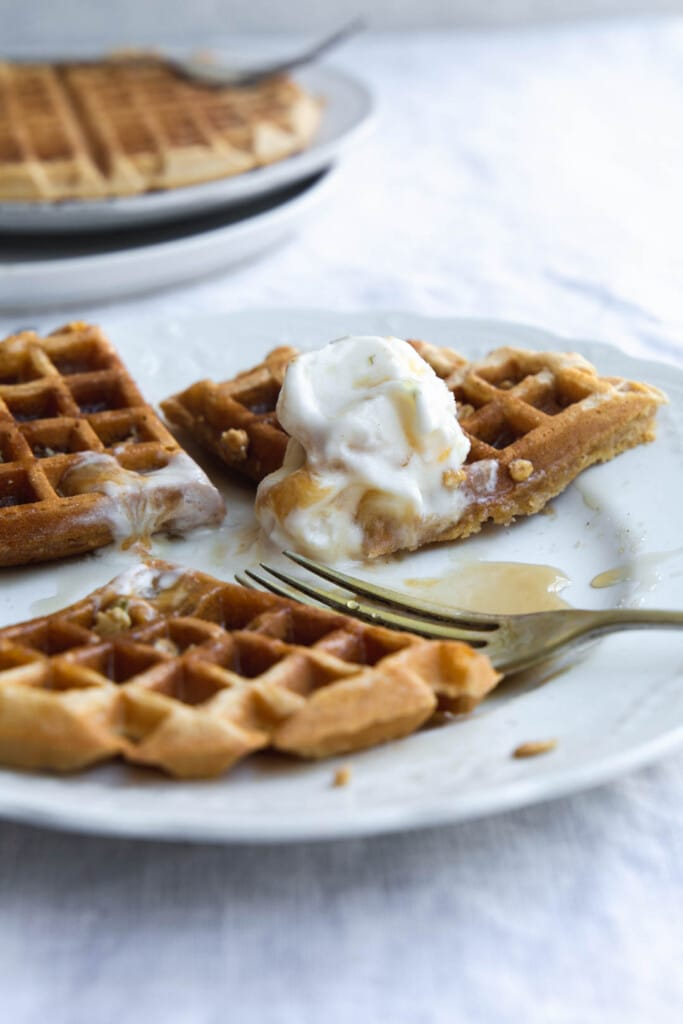 Close-up image of a vegan pumpkin waffles with melting ice-cream and maple syrup partially eaten on a white plate.