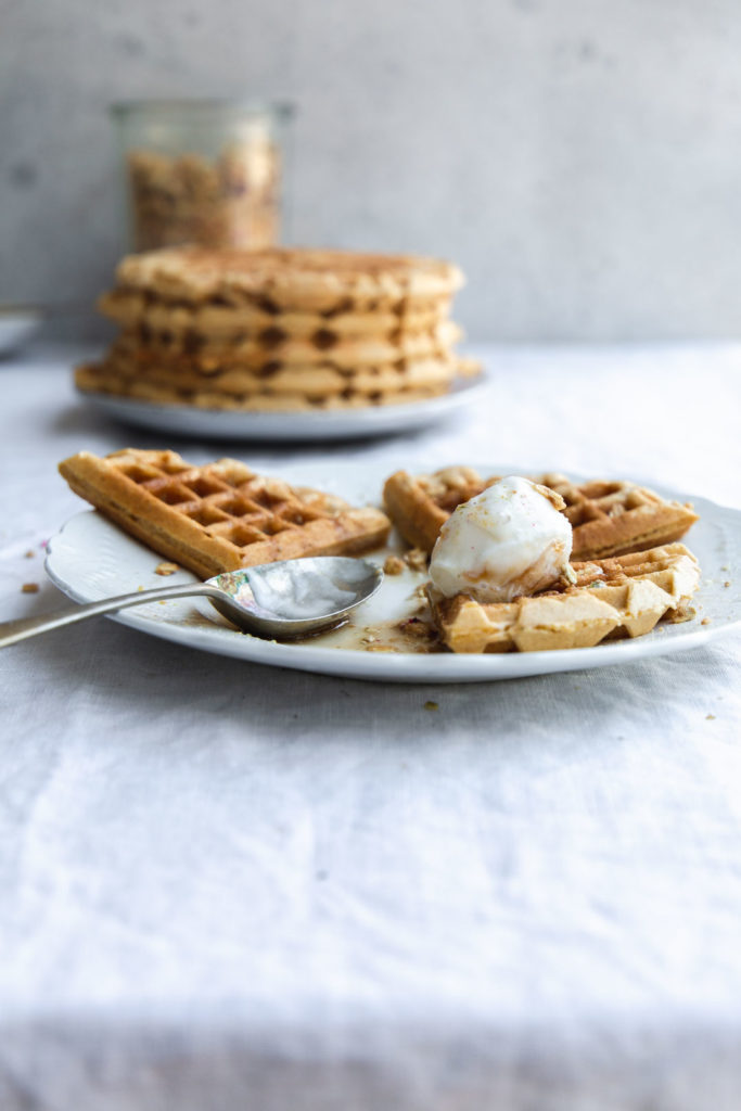 A table top image from the front of a plate holding a partially eaten serve of vegan pumpkin waffles with ice-cream and maple syrup. A stack of pancakes and a jar of granola sit in the background on a crinkled linen tablecloth.