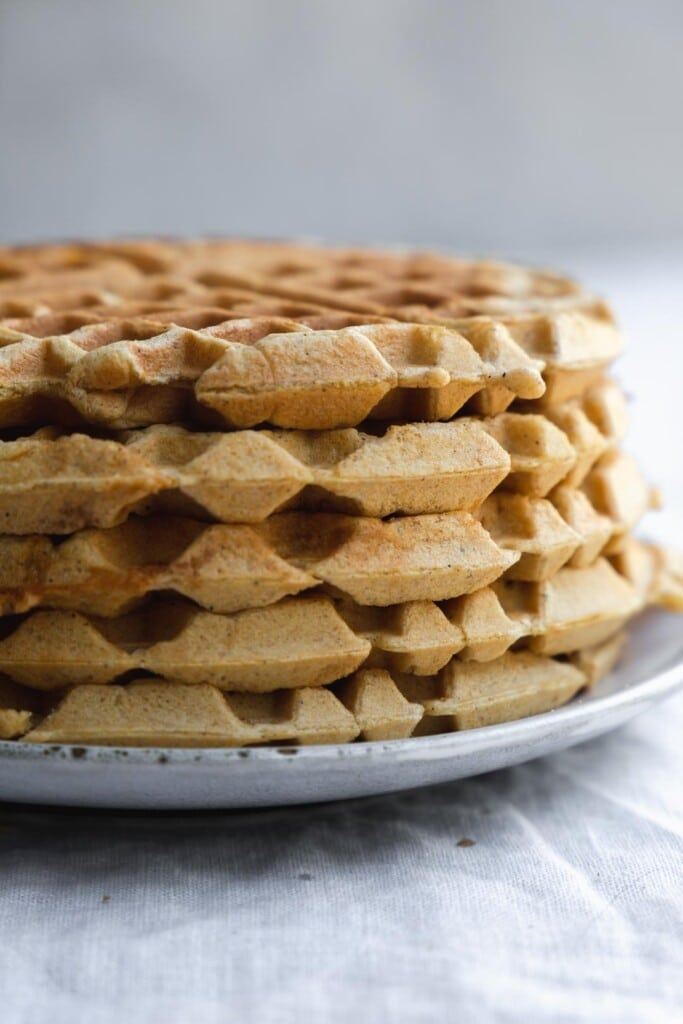 A super close up image of a stack of vegan pumpkin waffles to show the crispy geometric patterns on the side