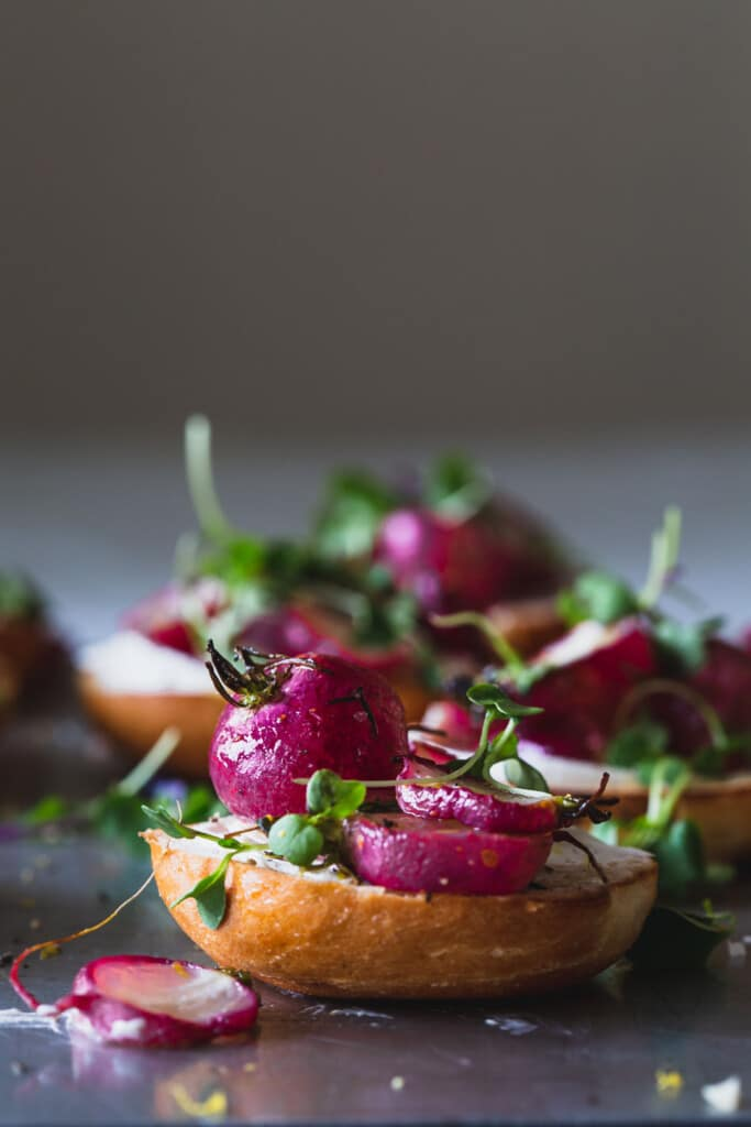 A front on image of a tray of roasted radishes sitting on mini bagels with cream cheese and micros greens. Front bagel in focus.