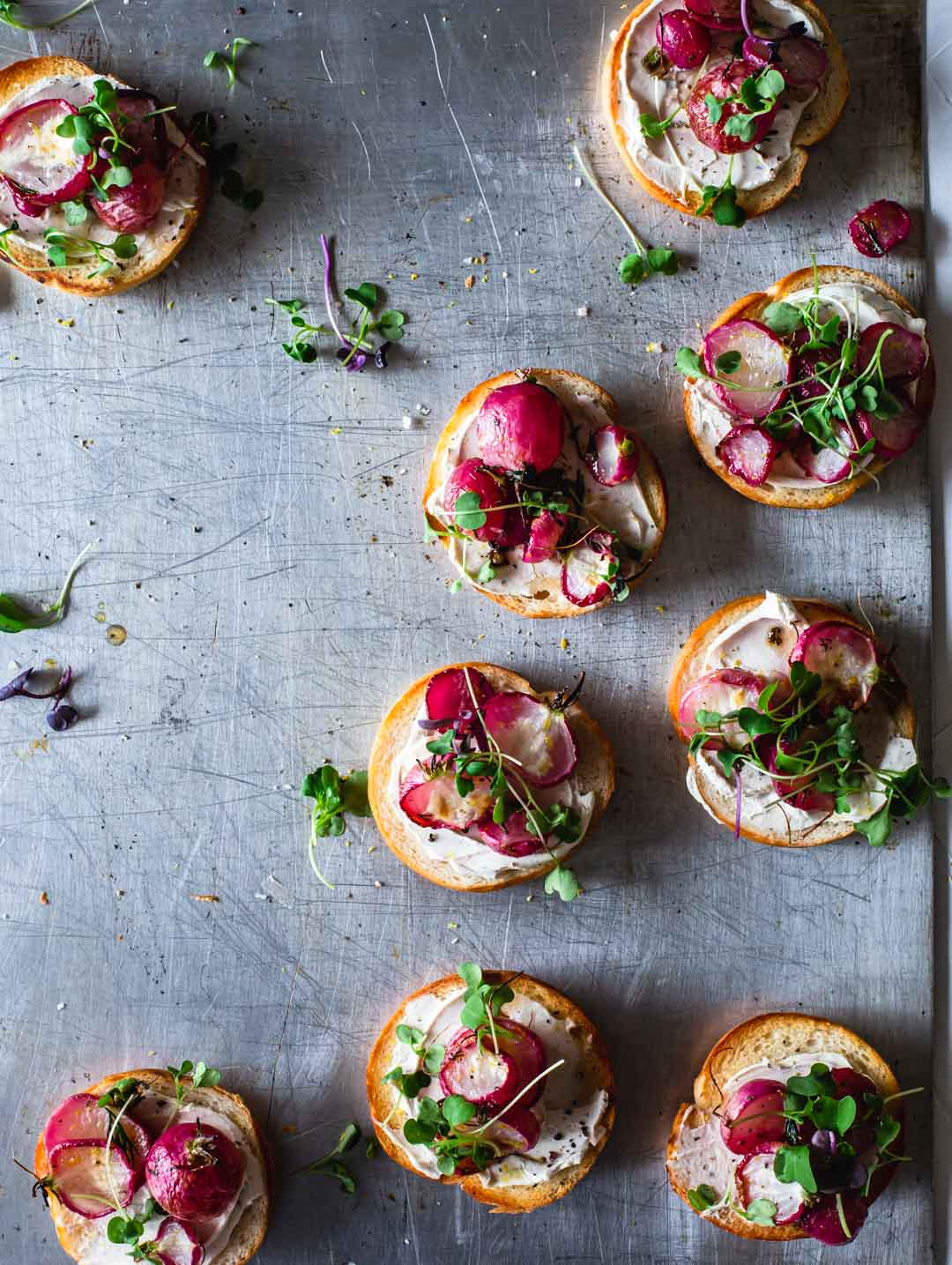 An overhead image of bagels with cream cheese and roasted radish