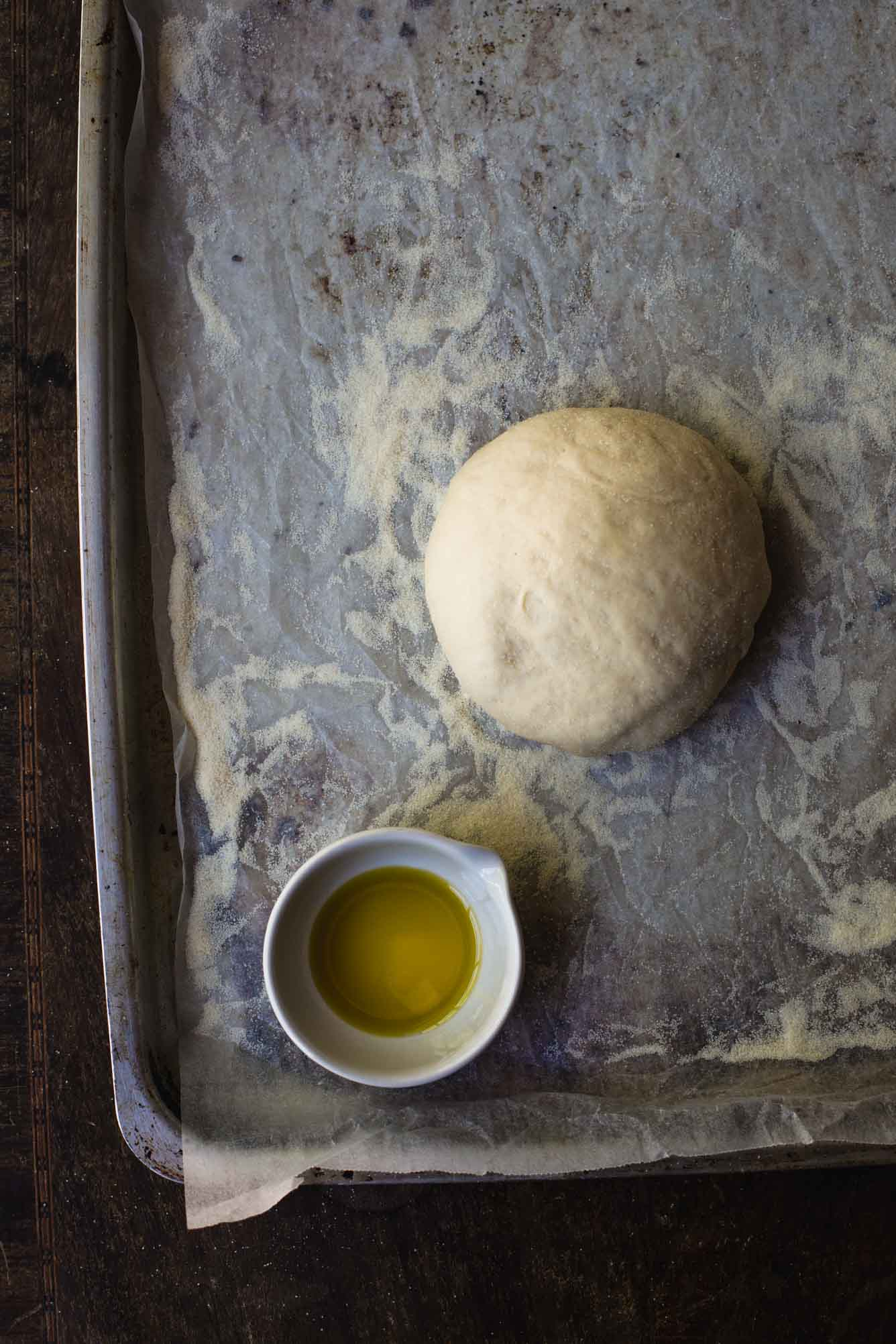 an overhead process image of a sheet pan lined with baking paper and a ball of pizza dough in the bottom left corner with a small bowl of olive oil sitting further off to the right. The baking paper is sprinkled with semolina