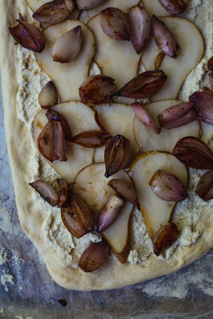 Overhead process image of the balasamic shallots sprinkled over the top of the pears on the white vegan pizza