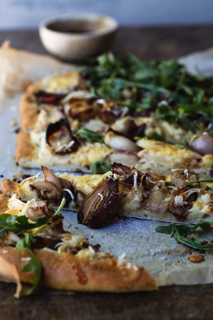 A close-up image of a cooked white vegan pizza sliced with the focus on a single slice and a balsamic shallot