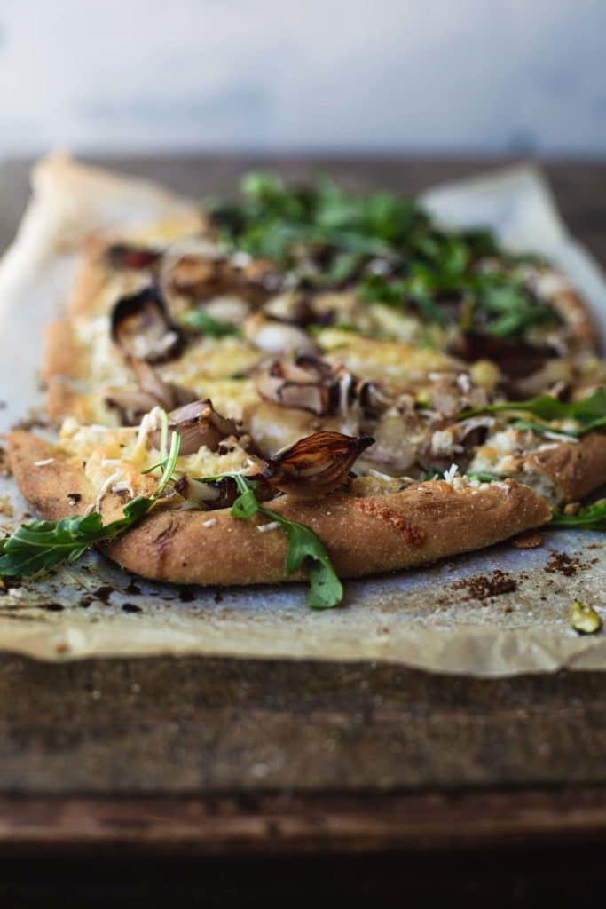 Front on close up image of a finished vegan white pizza sitting on baking paper on a rustic wooden table
