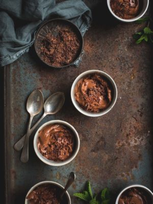 Small white bowls of chocolate mousse on a rusted background