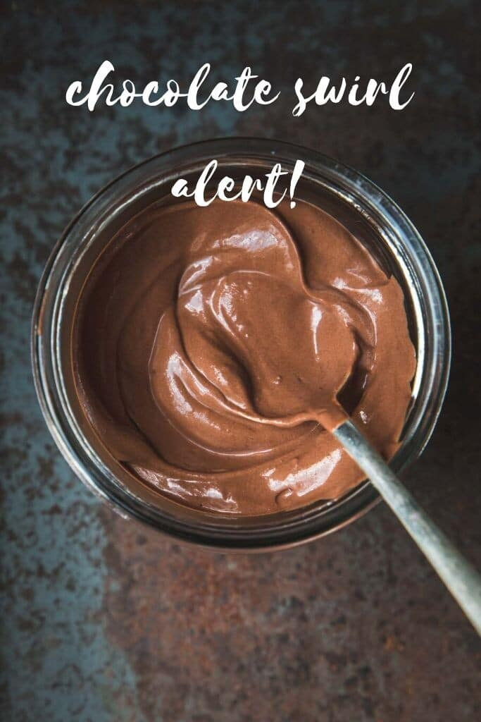 "Close-up overhead image of a large jar of vegan chocolate mousse swirled inside with a spoon sitting on an angle. The words ""chocolate swirl alert"" is written in white."
