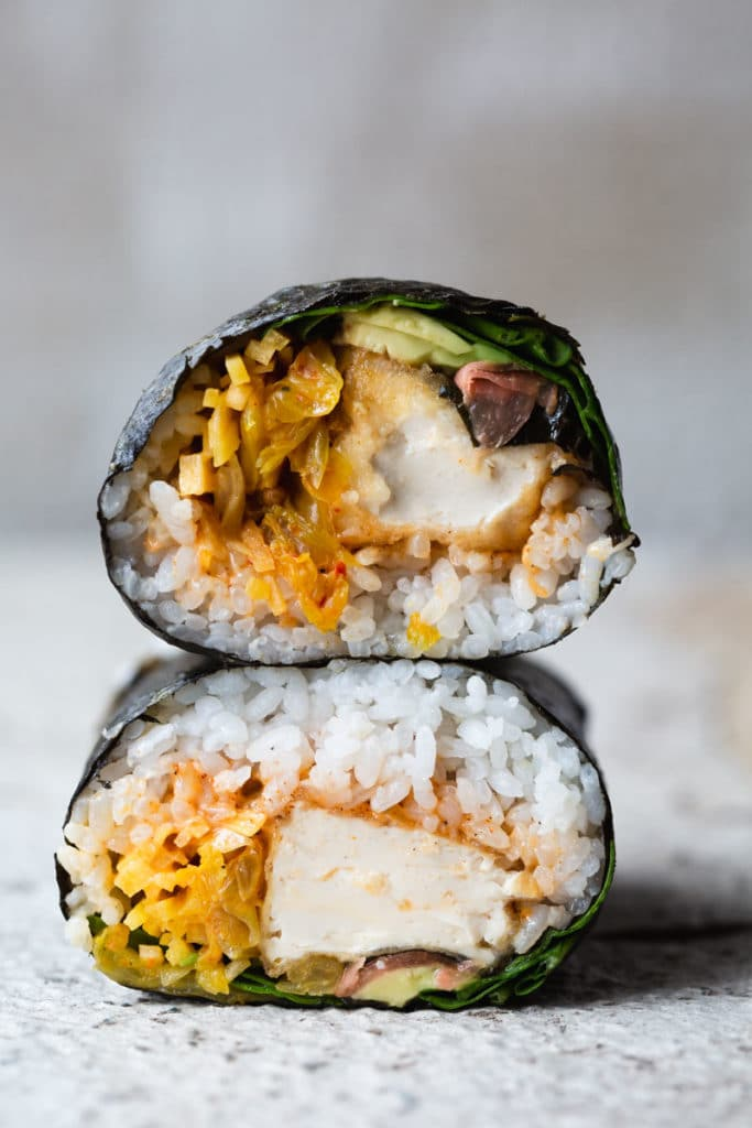 A close-up image of a crispy tofu sushi burrito wrapped in seaweed cut in half with the pieces stacked on top of each there to reveal the tofu, avocado, kimchi and rice.
